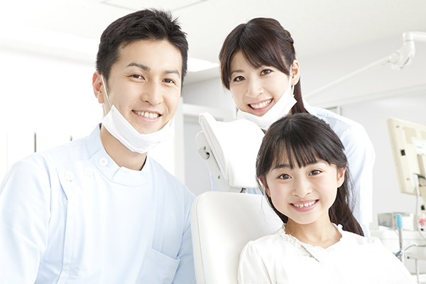 笑顔のユニフォーム姿の歯科医師